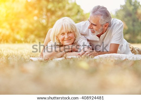 Two senior citizens relaxing in summer in the garden on a blanket - stock photo