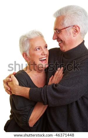 Two senior citizens smiling at each other - stock photo