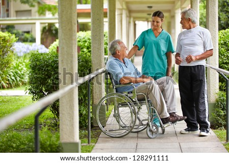 Two senior citizens talking to a nurse in a hospital garden - stock photo