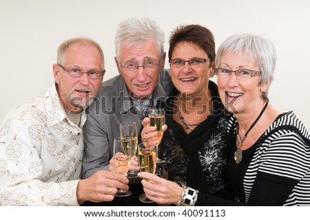 Two senior couples toasting on a Happy New Year. - stock photo