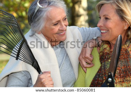 two senior friends gardening - stock photo