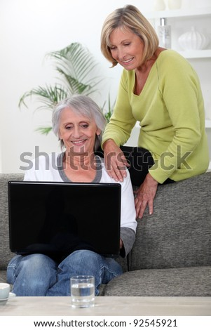 two senior friends relaxing at home - stock photo
