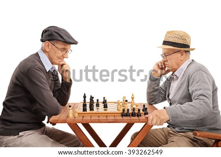 Two senior gentlemen playing chess and contemplating their next move isolated on white background - stock photo