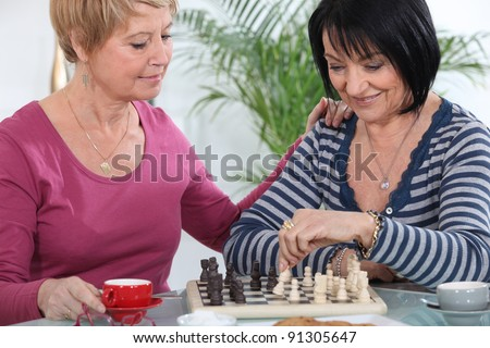 two senior girlfriends playing chess - stock photo