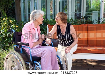 Two senior ladies chatting on a garden bench with one sitting in a wheelchair at the end as they enjoy a day outdoors in the shade of a tree - stock photo
