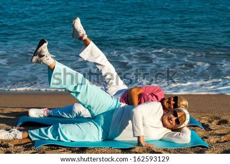Two senior ladies doing leg stretching exercise on beach. - stock photo