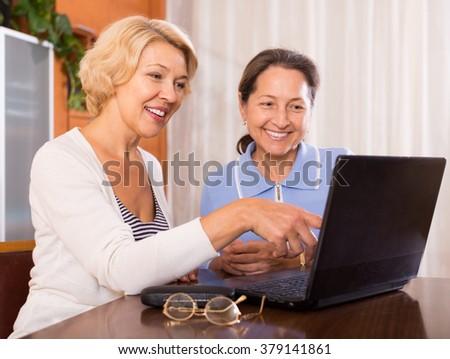 Two senior ladies with laptop buying something online. Focus on blonde - stock photo