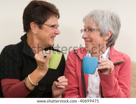 Two senior lady's drinking coffee together and having a good time. - stock photo