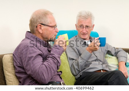 Two senior men drinking coffee and discussing some things. - stock photo