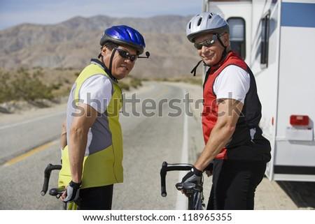 Two Senior men with bikes on road - stock photo