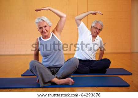 Two senior people doing gymnastics in a gym - stock photo