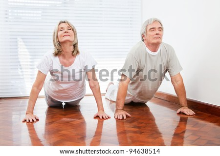 Two senior people doing yoga exercise Bhujangasana in gym