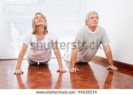 Two senior people doing yoga exercise Bhujangasana in gym - stock photo