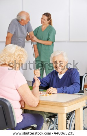 Two senior people playing Bingo together in a nursing home - stock photo