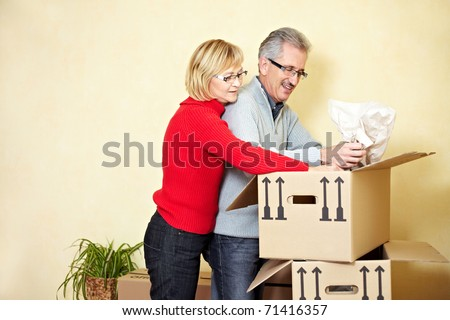Two senior people searching stuff in a moving box - stock photo