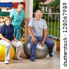 Two senior people sitting on gym ball in physiotherapy - stock photo