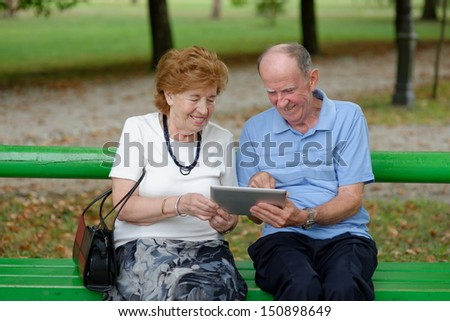 Two senior people sitting with a tablet PC in a nature park  - stock photo