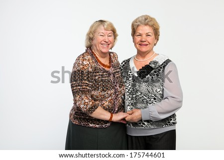 two senior woman friends studio portrait with  isolated on white - stock photo
