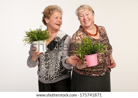 two senior woman friends studio portrait with plants in the pot isolated on white