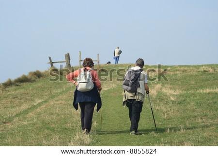 Two senior women enjoying a walk on a coast path. - stock photo