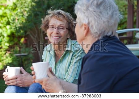 Two senior women enjoying a warm drink outdoors - stock photo