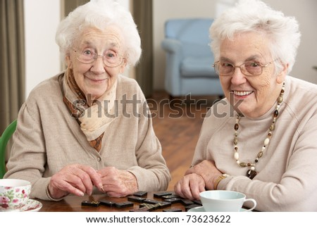 Two Senior Women Playing Dominoes At Day Care Centre
