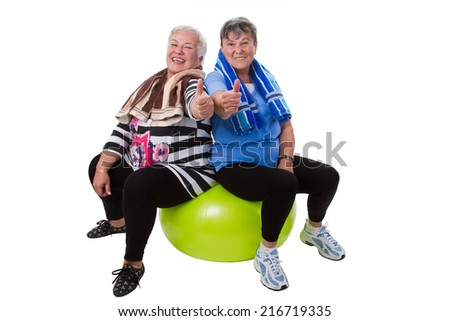 Two senior women sitting on a fitness ball - isolated - stock photo