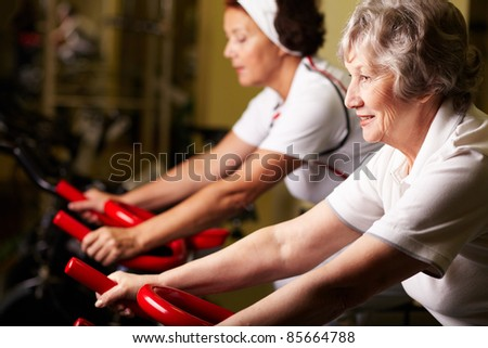 Two senior women training in gym - stock photo