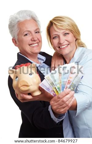 Two senior women with Euro money bills and piggy bank - stock photo