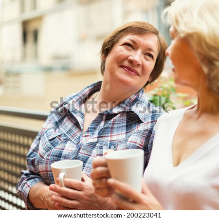 Two seniore women drinking coffee on balcony and smiling - stock photo