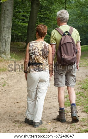 Two seniors are strolling through the woods.