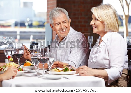 Two seniors eating out in restaurant with their children