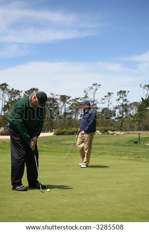 Two seniors enjoying a game of golf and putting on the green - stock photo