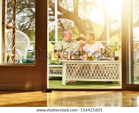 two seniors having dinner on patio. - stock photo