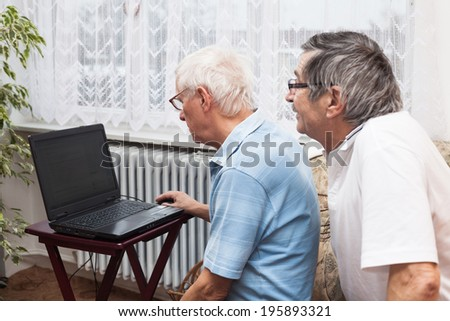 Two seniors learning to use a computer.