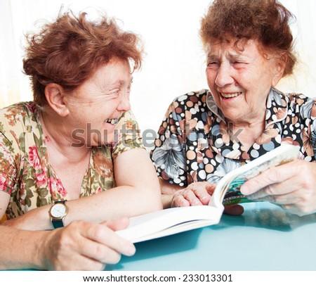 Two seniors. Old woman reading book. Friendship elderly - stock photo