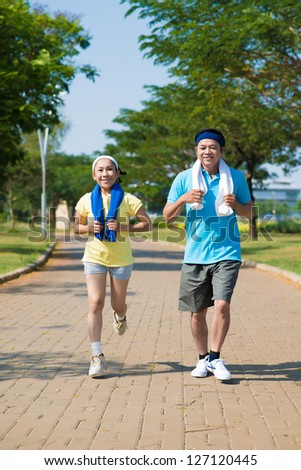 Two seniors running in the park - stock photo