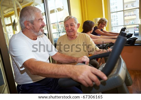 Two Seniors talking while in a gym - stock photo