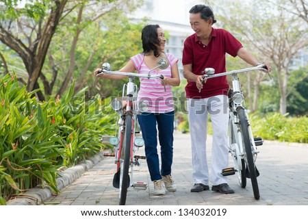 Two seniors walking with bicycles on the road - stock photo