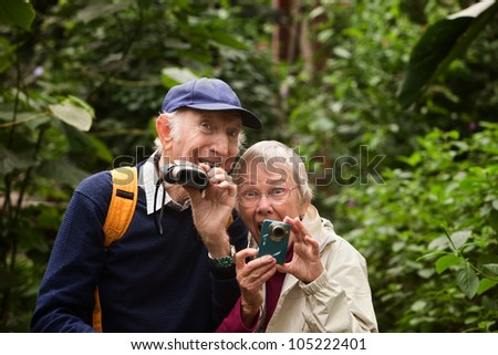 Two seniors with camera and binoculars in forest - stock photo