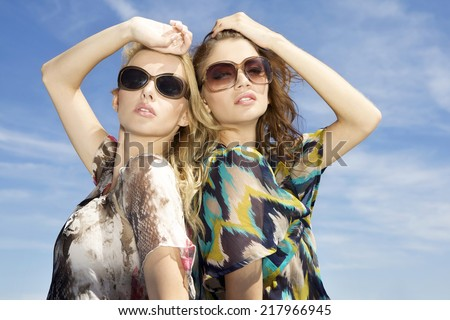 two sensuality beautiful young adult pretty brunette and blonde girl friends in sunglasses and summer dress on background blue sky - stock photo