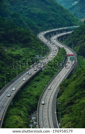Two separate elevated roads running between mountains and trees. - stock photo