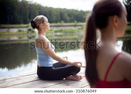 Two serene beautiful sporty fit young women working out on the lake on summer day, Sitting in Easy (Pleasant Posture), Sukhasana, meditating with closed eyes, breathing, back view - stock photo