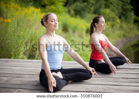 Two serene young beautiful women on meditation session outdoors, sitting cross-legged in Ardha Padmasana Posture, working out in park on summer day, practicing pranayama with closed eyes, full length - stock photo