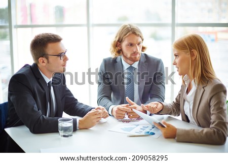 Two serious businessmen listening to their colleague at meeting in office - stock photo