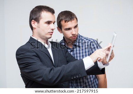 Two serious businessmen looking at digital tablet.