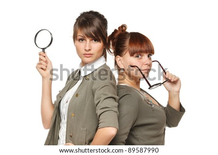 Two serious girls standing with magnifying glass and old fashioned eyeglasses, isolated on white background - stock photo