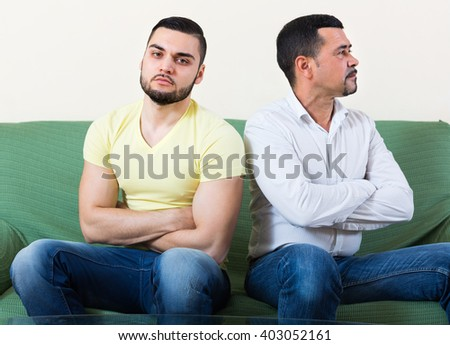 Two serious men sitting on couch and being at odds. Selective focus - stock photo