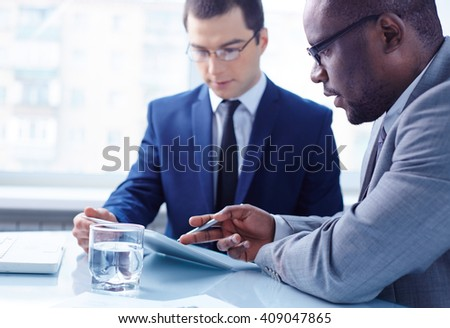 Two serious partners discussing their plans with touchpad - stock photo
