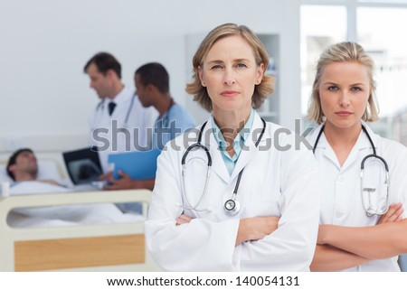Two serious women doctors standing in front of medical team and a patient